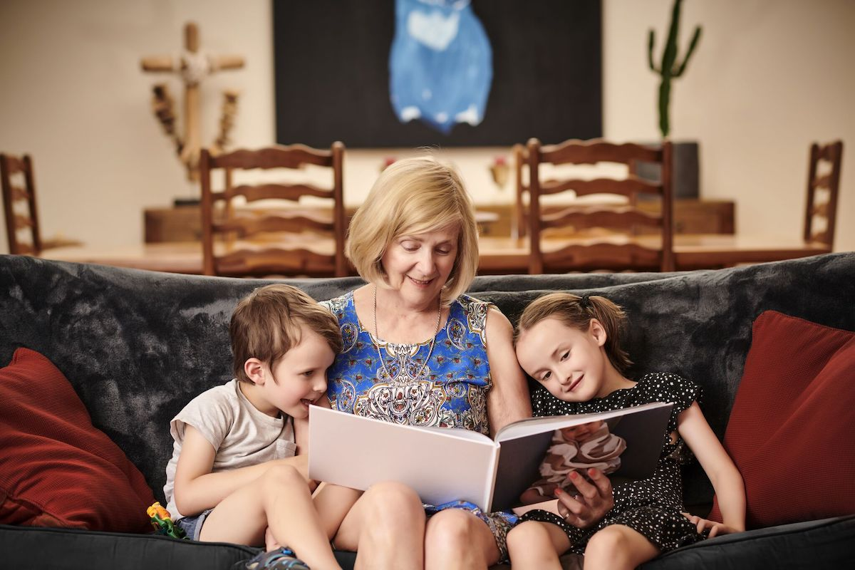 A woman and two young children sitting on a couch looking at photobooks