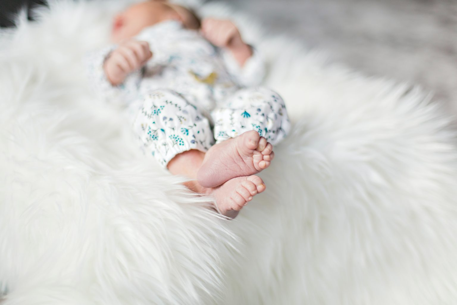 Up close photo of baby feed on a fluffy white rug with their face hidden