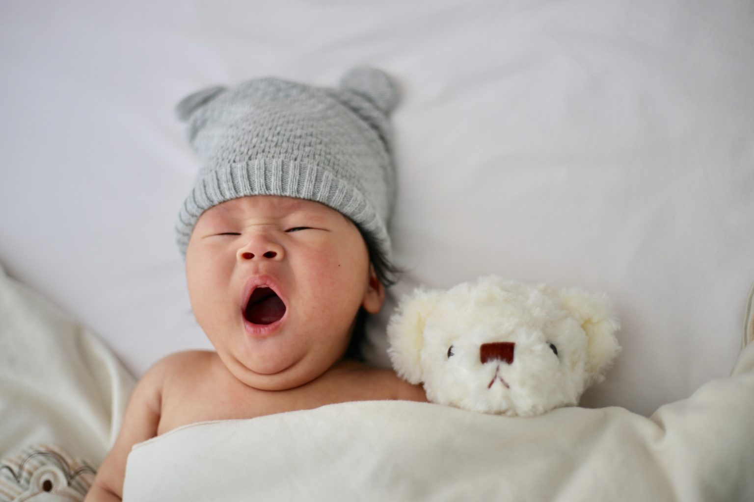 Small baby yawning with a grey beanie and a stuffed teddy tucked in bed next to it