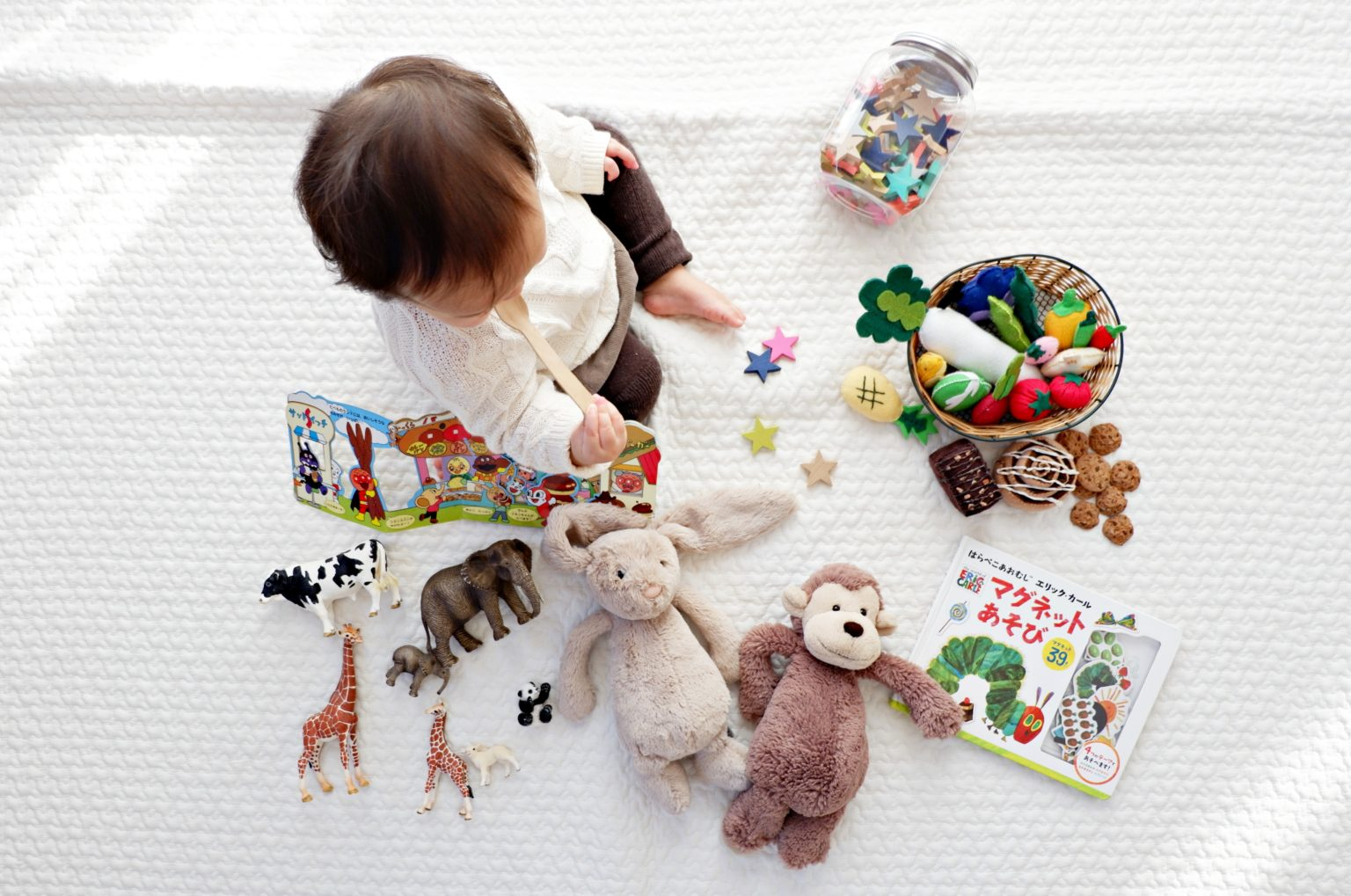 Small child playing with toys on a white mat
