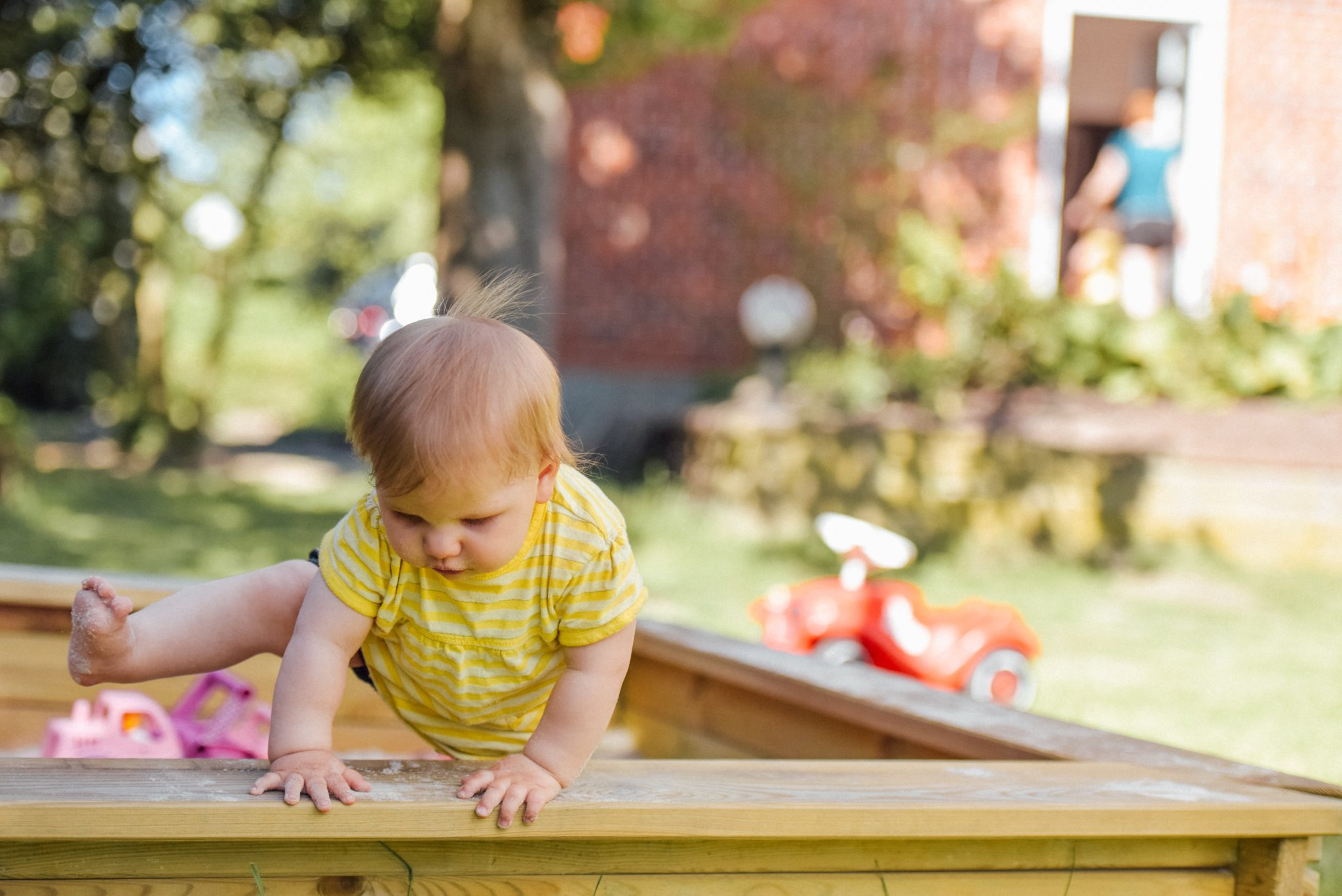 baby trying to climb out of the sandpit