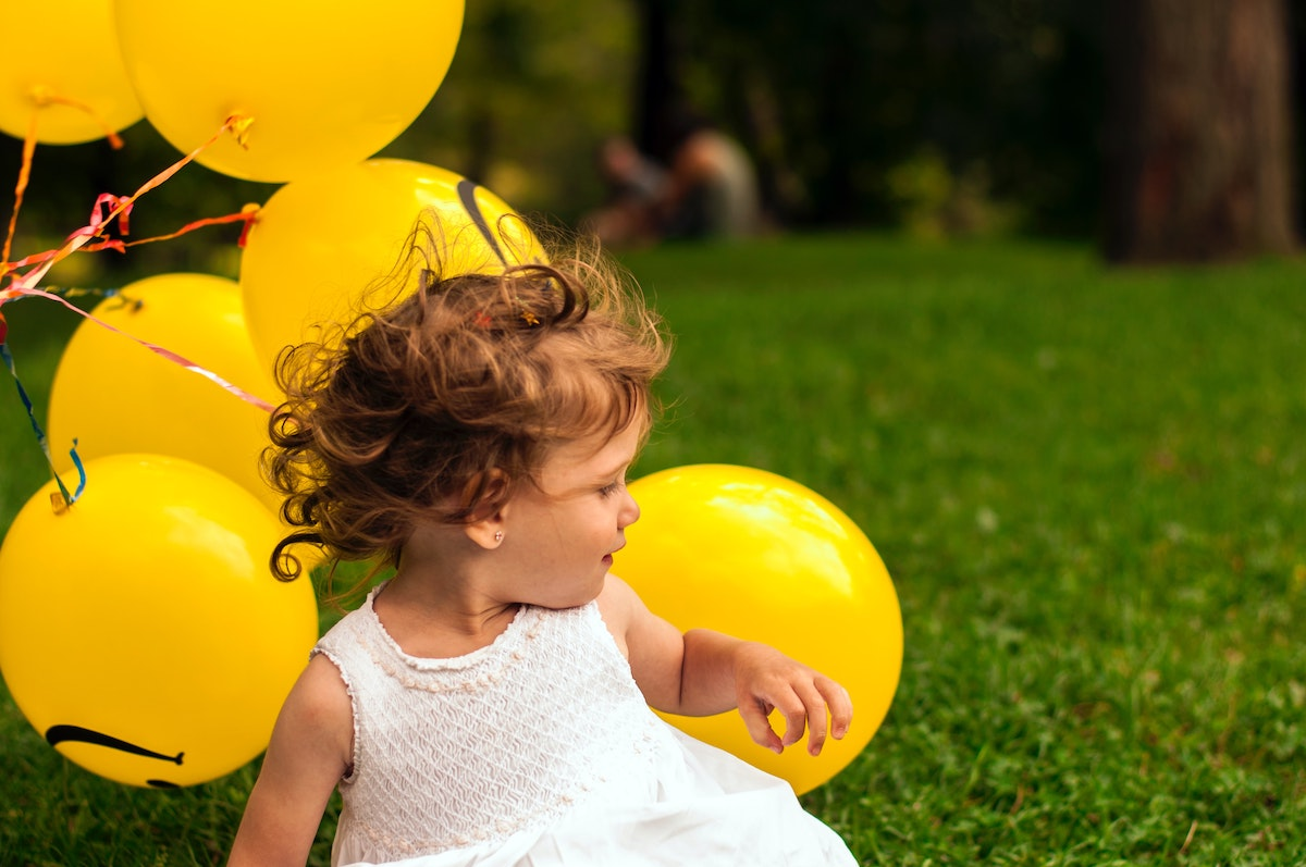 small child sitting on the grass outside with yellow balloons in the background while looking away at the camera