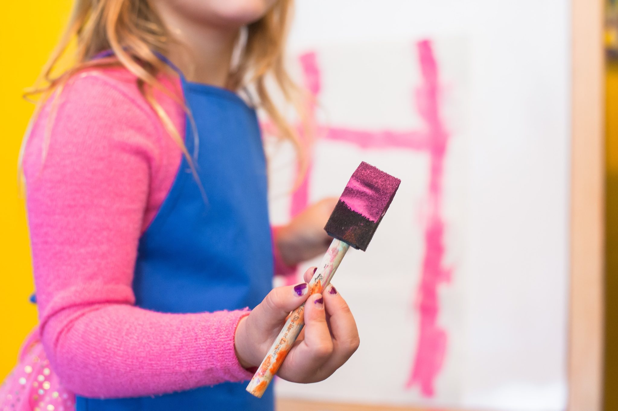 A girl wearing a blue apron holding onto a pink paint brush having fun with her face slightly hidden