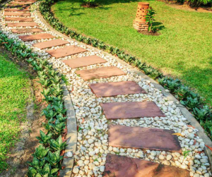Hardscaped walk way with river rocks and pavers in beautiful landscaping