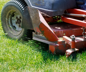 red lawn mower close up going over grass in gainesville florida yard maintenance