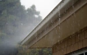 rain pouring out of white rain gutters on side of house