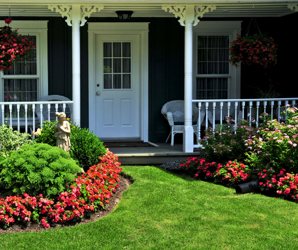 Exterior of a charming home surrounded by flower beds and a patio