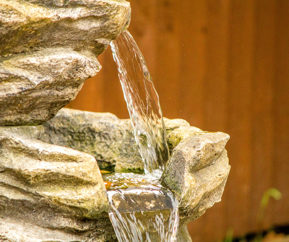 A stone tiered water feature pouring clear water