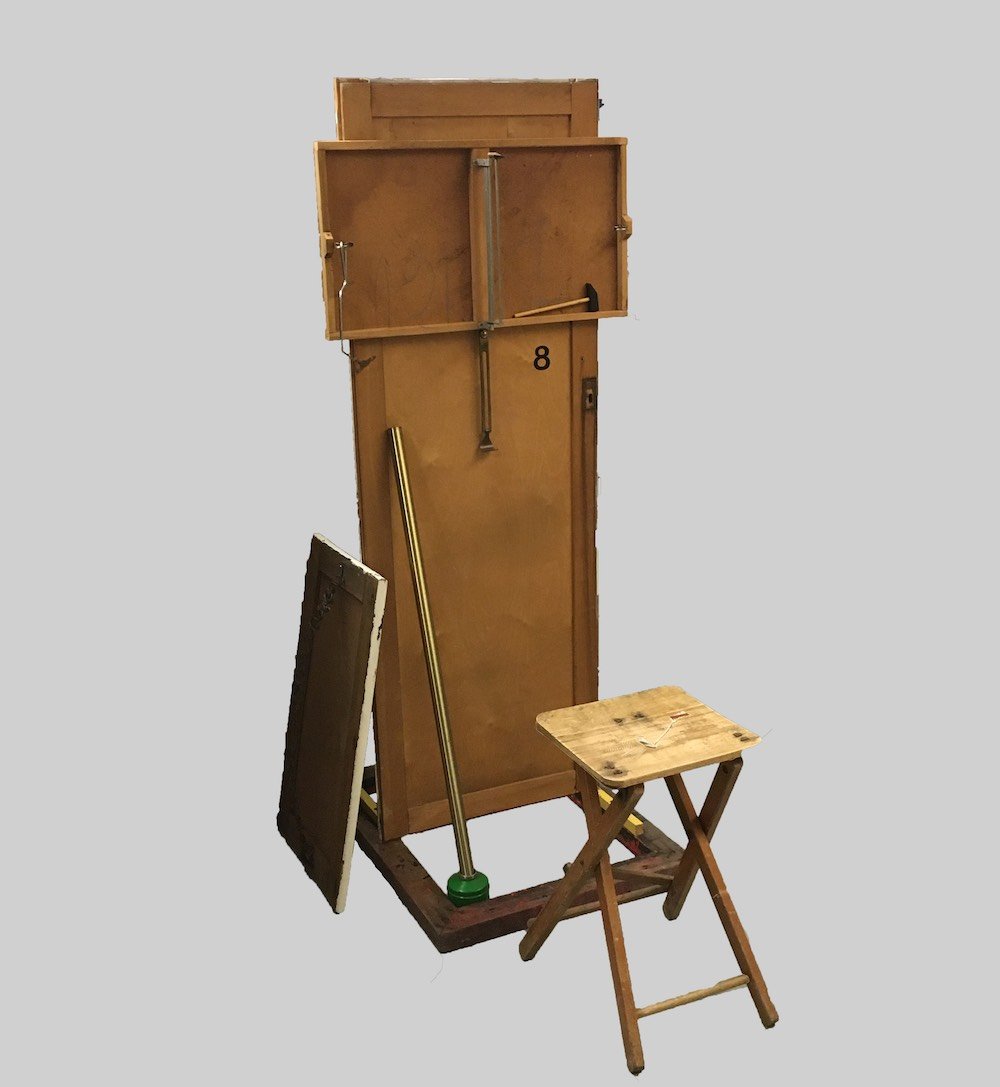 """Joseph Bradley Hill's sculpture """"Arms & Legs"""", a human-sized sculpture made from a wooden door mounted on a screen printing frame with various appendages including a toy hammer, vinyl sticker and door knocker."""