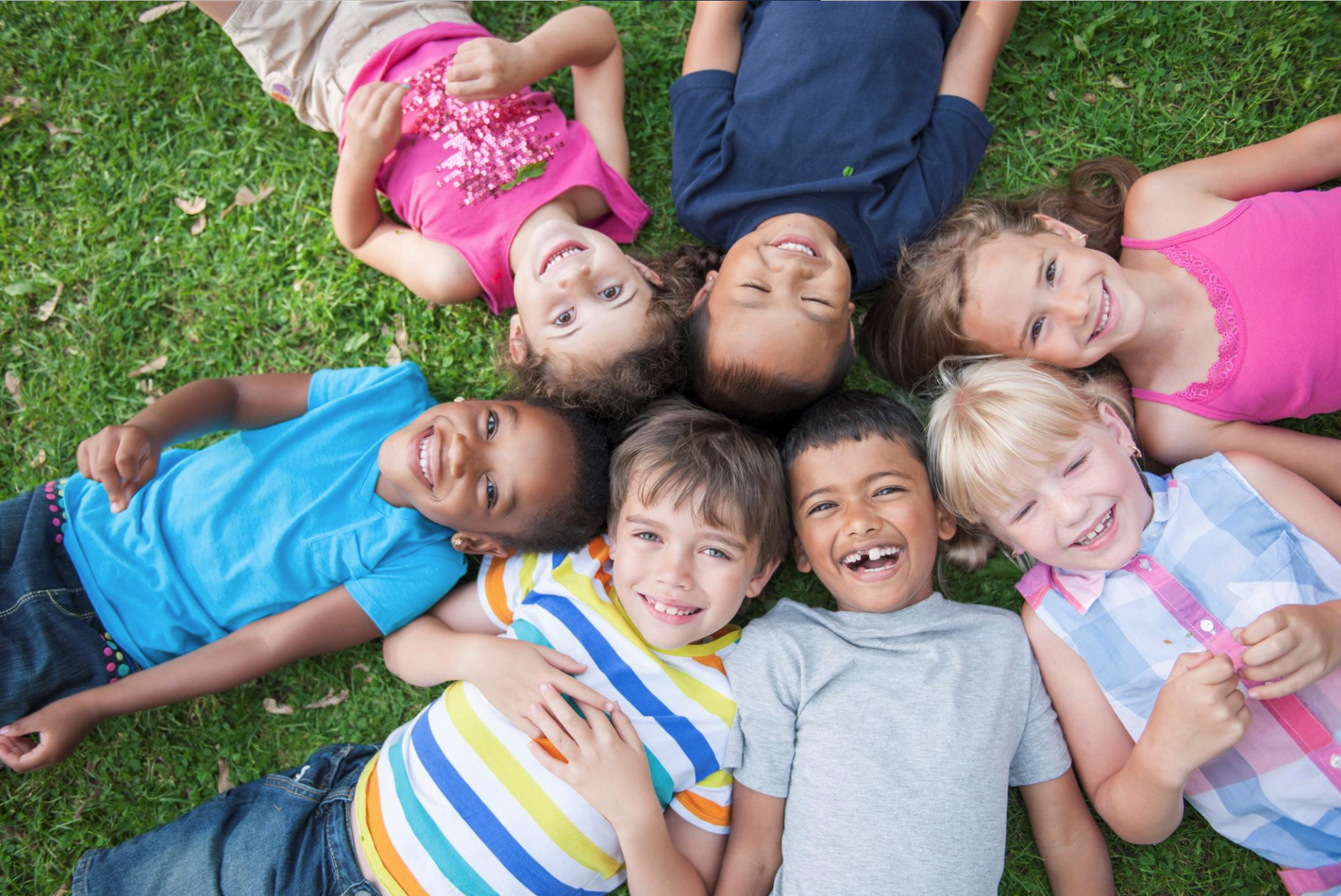 smiling children lying on the grass in a circle