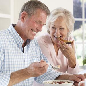 elderly couple enjoying food with new dental bridge