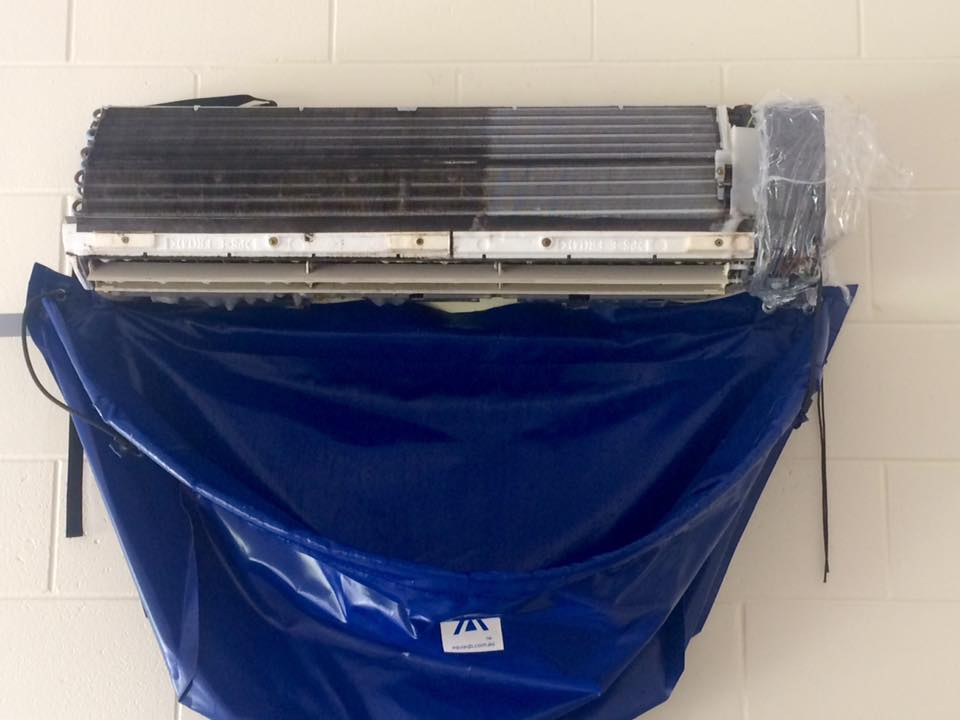 Mouldy air conditioner half way being cleaned with blue water catchment bag underneath