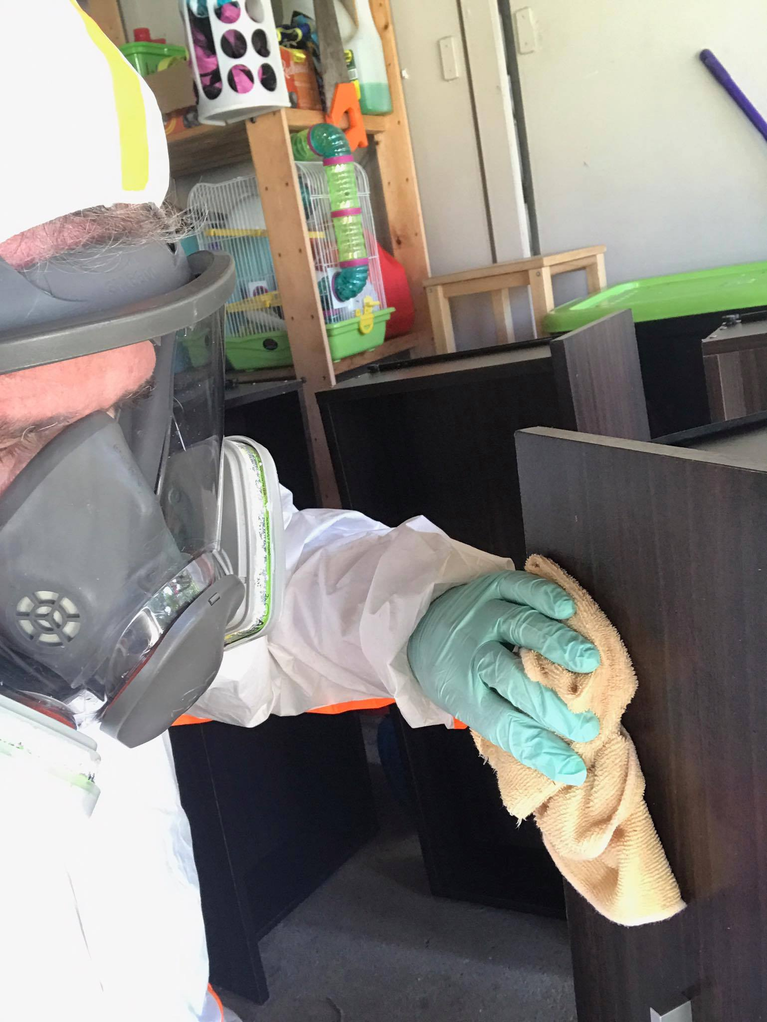 Wayne cleaning mouldy furniture in full PPE