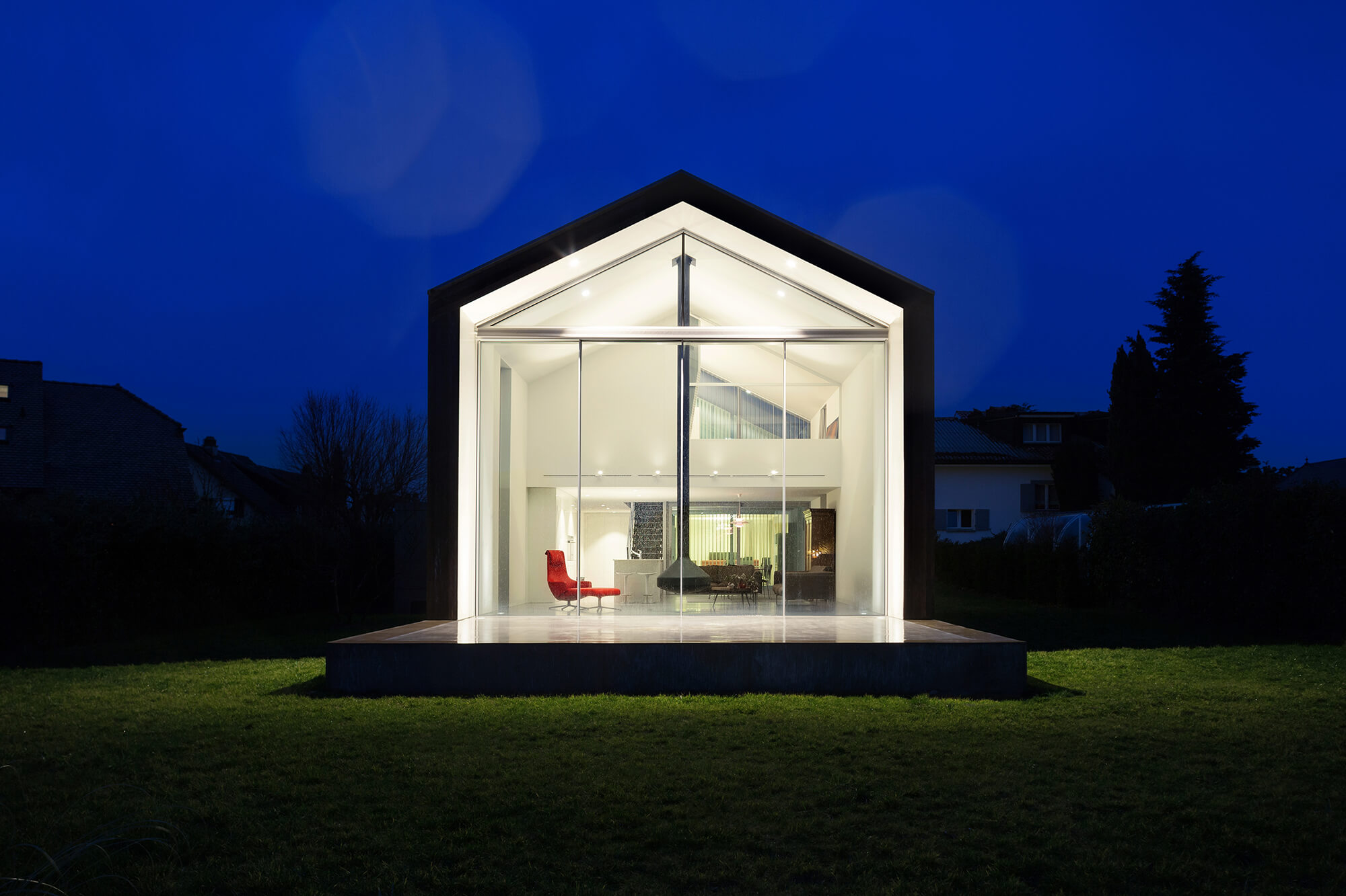 An architecturally designed home with warm interior lights bright against the deep blue evening sky.