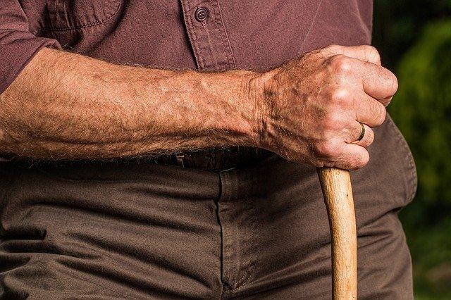Bras d'une personne âgée qui tient un bâton de marche
