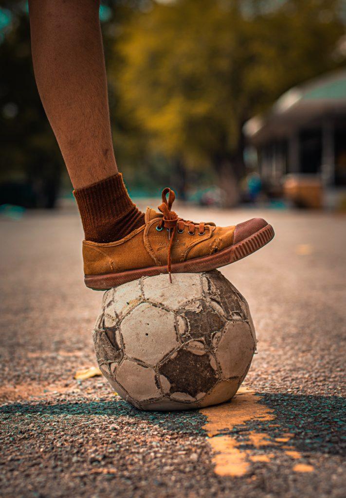 Pieds d'un enfant sur un ballon de foot abimé