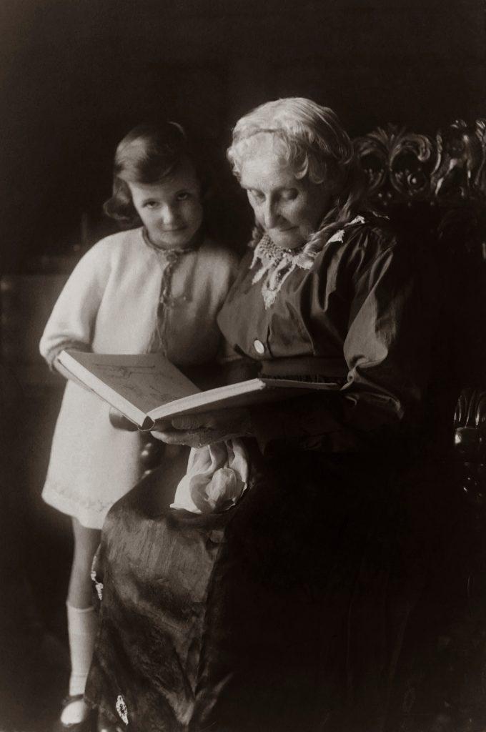Petite fille avec sa grand-mère lisant un livre