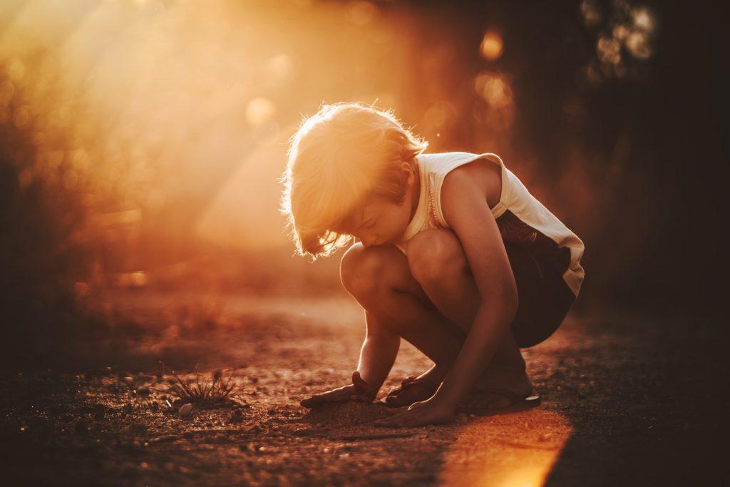 Petit garçon qui joue avec la terre