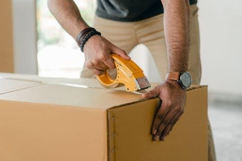 Crop faceless young male with wristwatch using adhesive tape while preparing cardboard box for transportation