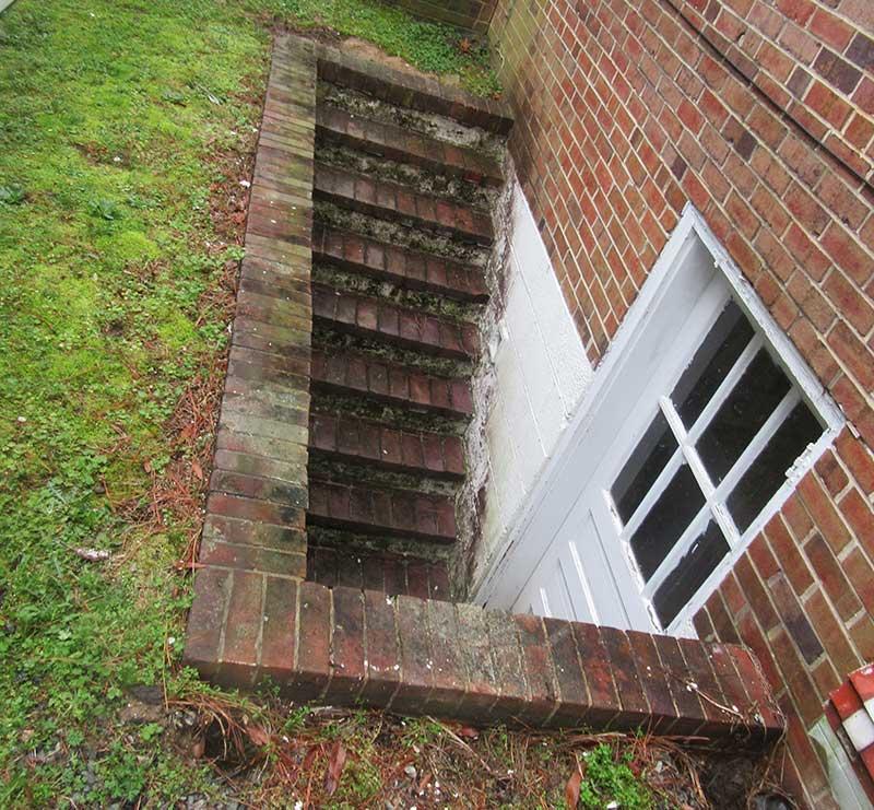 Brick basement open stairwell before Vinyl Window Wells vinyl stairwell cover