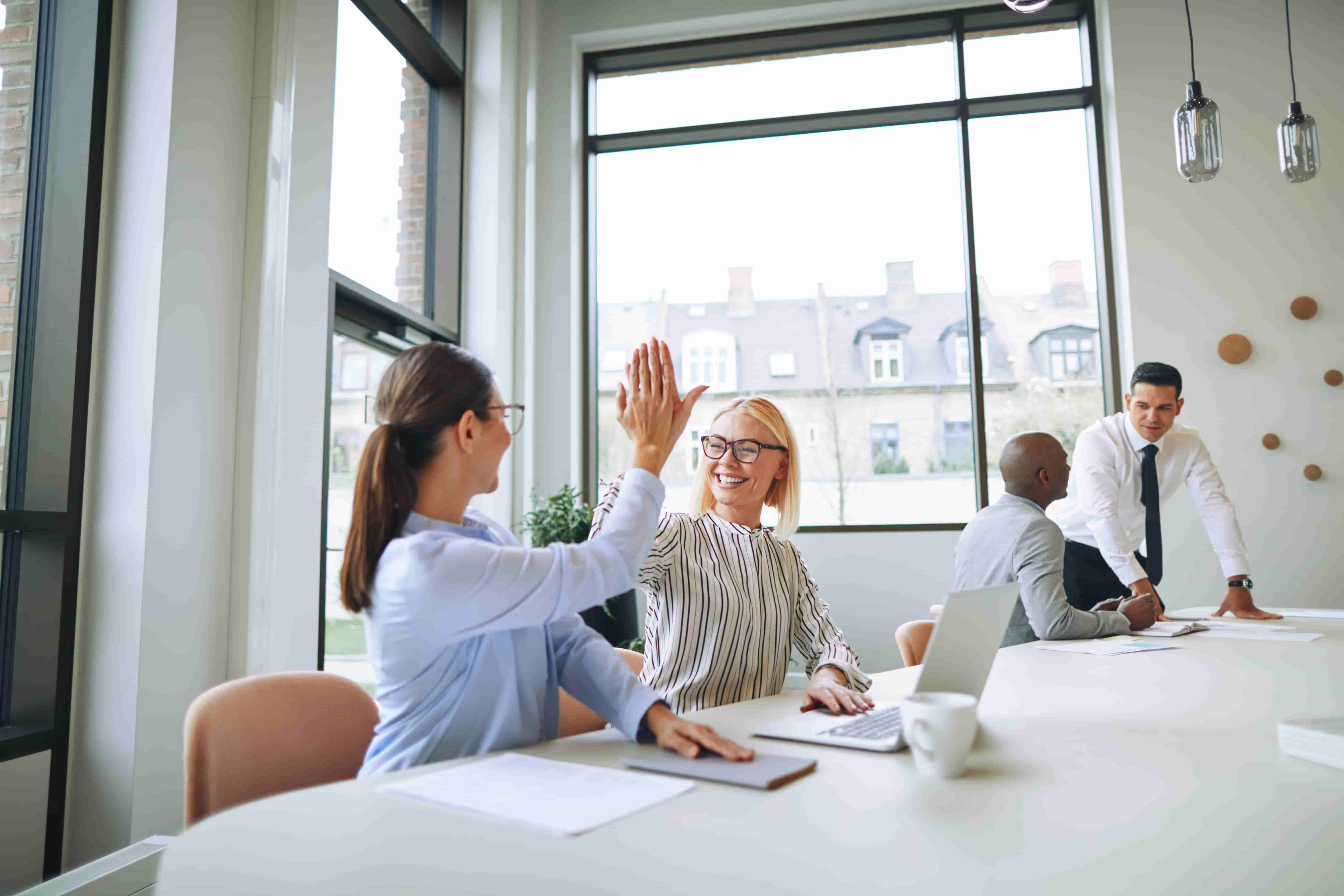 Two employees high fiving for digital boardroom