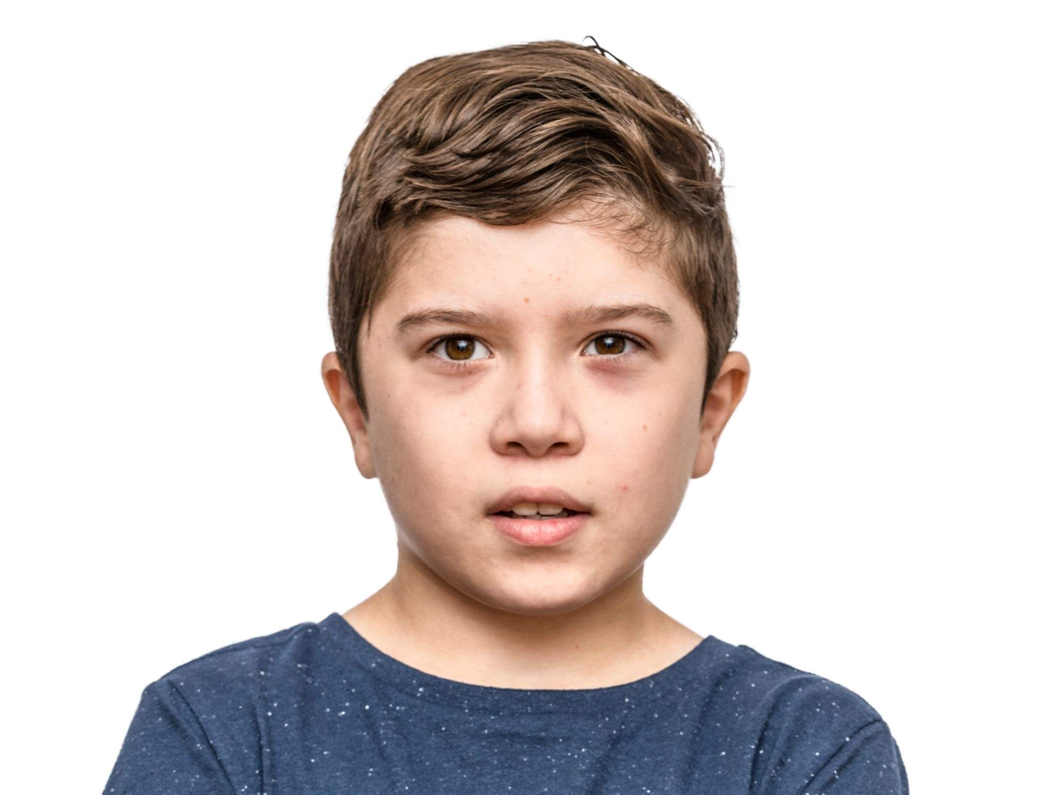 young teenage boy with autism looking at camera slightly smiling