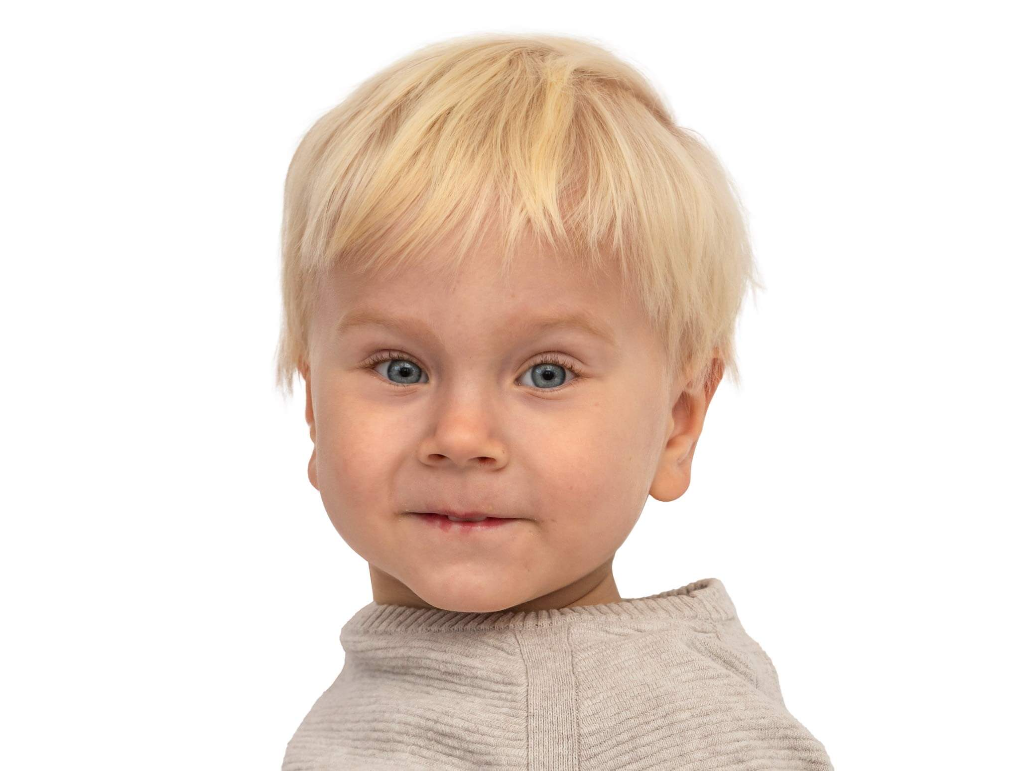 toddler boy with autism looking at camera slightly smiling