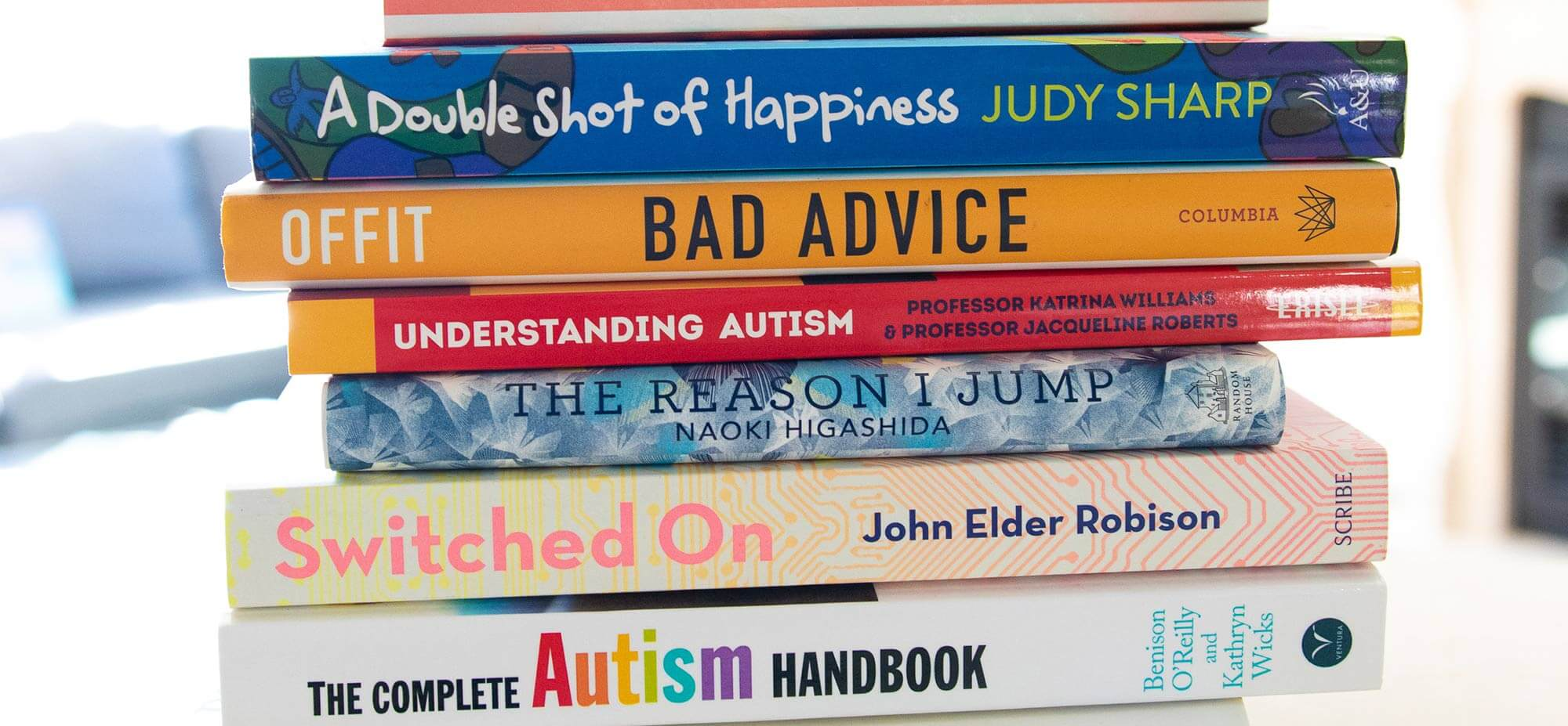Stack of books about autism with spines showing