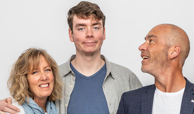 young adult male with autism standing with mum and dad, dad looking up at him