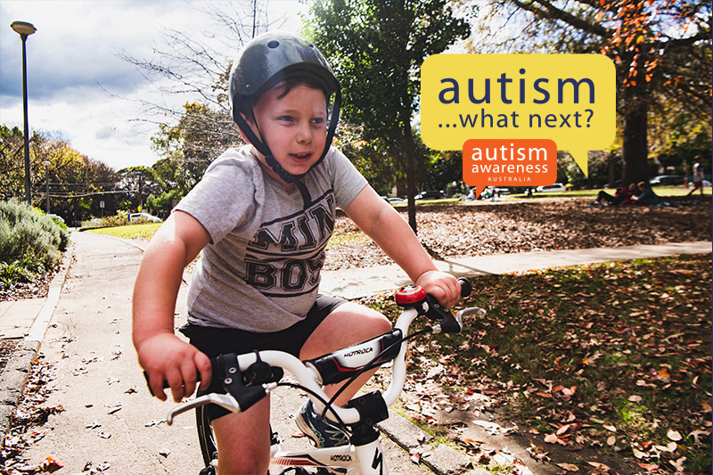 Boy with autism riding bike with Autism What Next logo