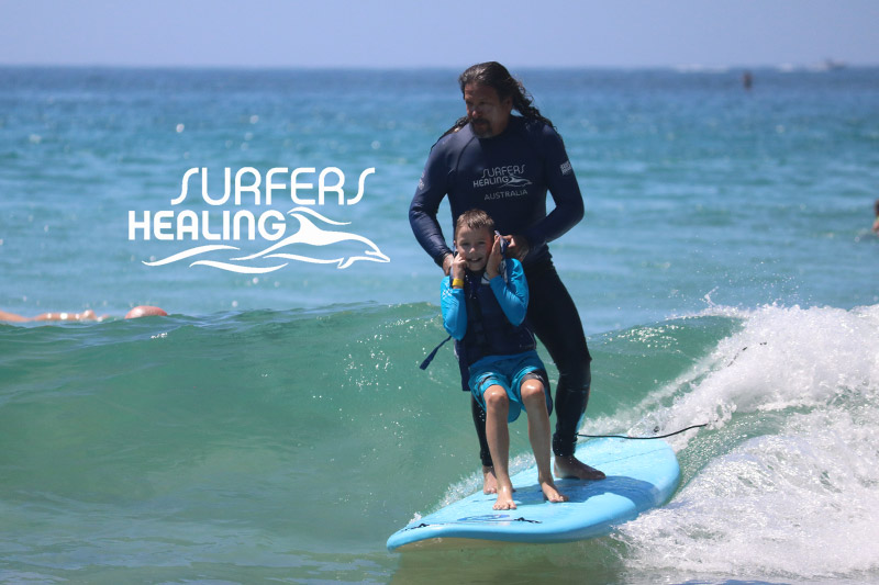 Child with autism and man riding waves together in the surf