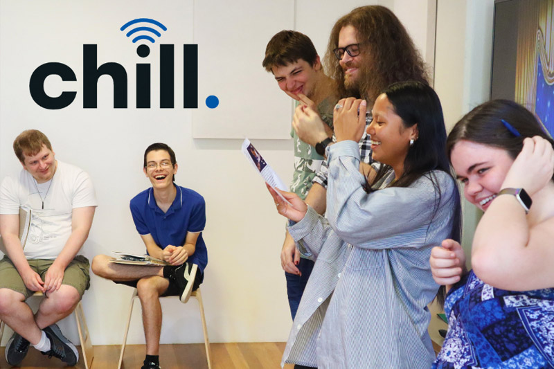Group of Chill participants laughing together in a room with the chill logo on the wall behind