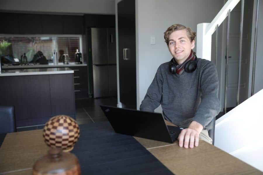 Young man sitting in kitchen with laptop