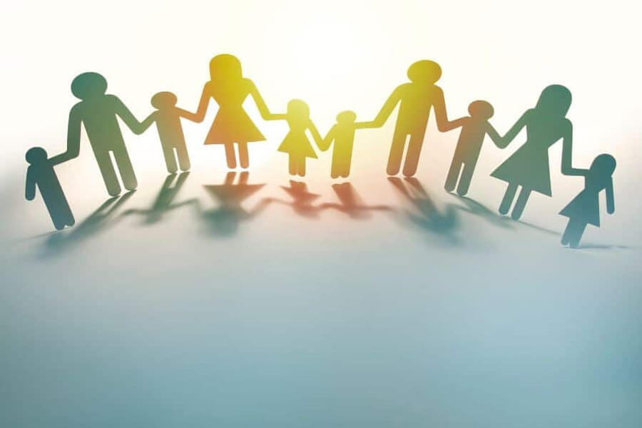 Concept image of a group of parents holding hands with children cut out of cardboard