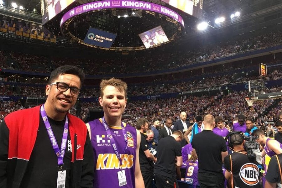 Young man with friend at indoor basketball stadium full of people