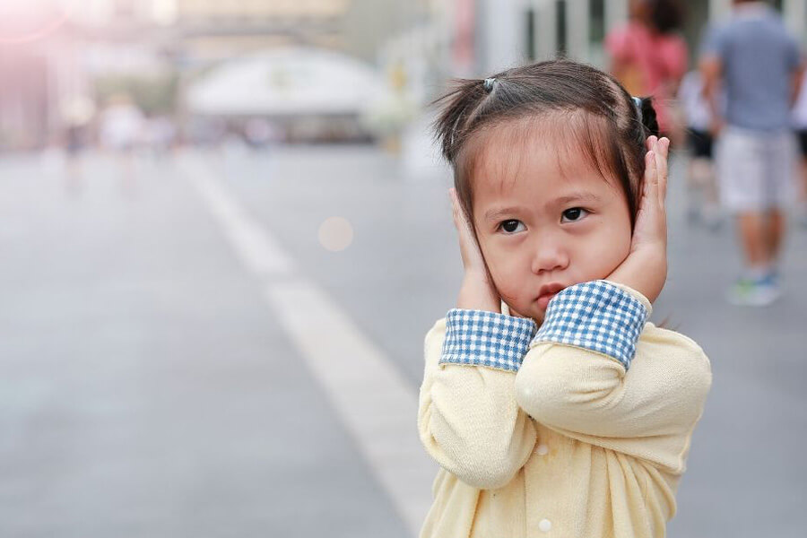 Small girl in city street with hands covering her ears