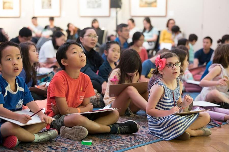 Room full of children sitting cross legged on the floor writing on boards