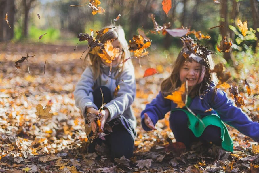 Two small girls playing with autumn leaves on the ground and laughing
