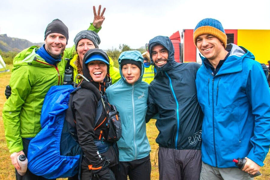 Group of young adults wearing wet leather gear and beanies laughing and hugging