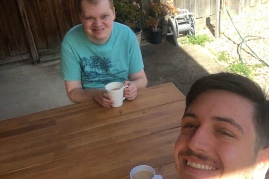 Selfie of two young adult men drinking coffee