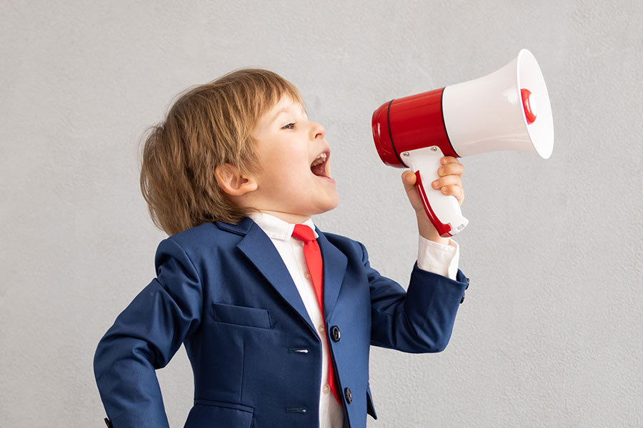 Young boy holding megaphone dressed in a suit