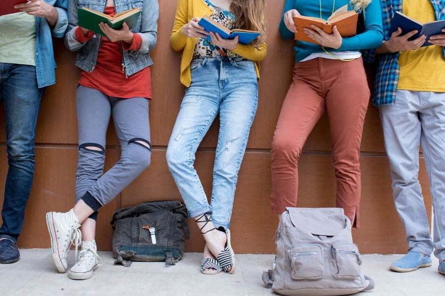 Group of young adults from waist down reading books