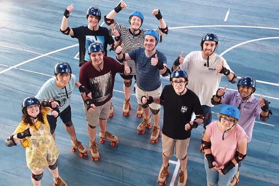 Group of people on roller skates giving thumbs up