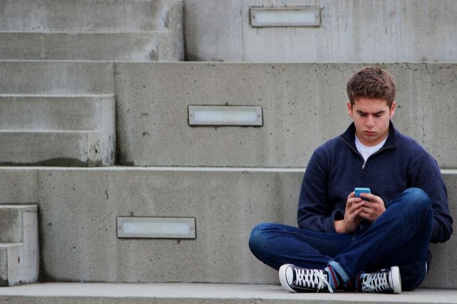 Teenager sitting on steps with phone in hand