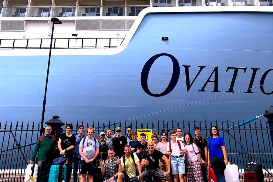 Group of people in front of cruise ship