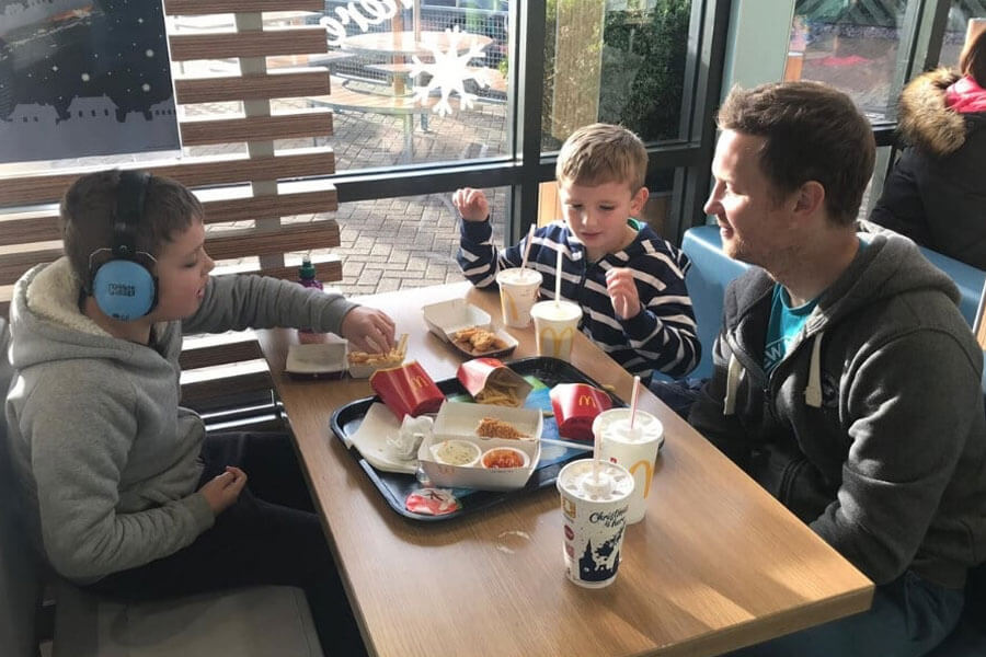 Dad sitting in fast food restaurant with two young boys, one wearing headphones