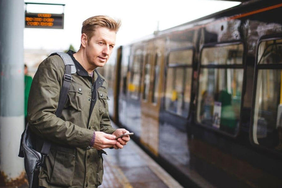 Young man on train station with phone in hand