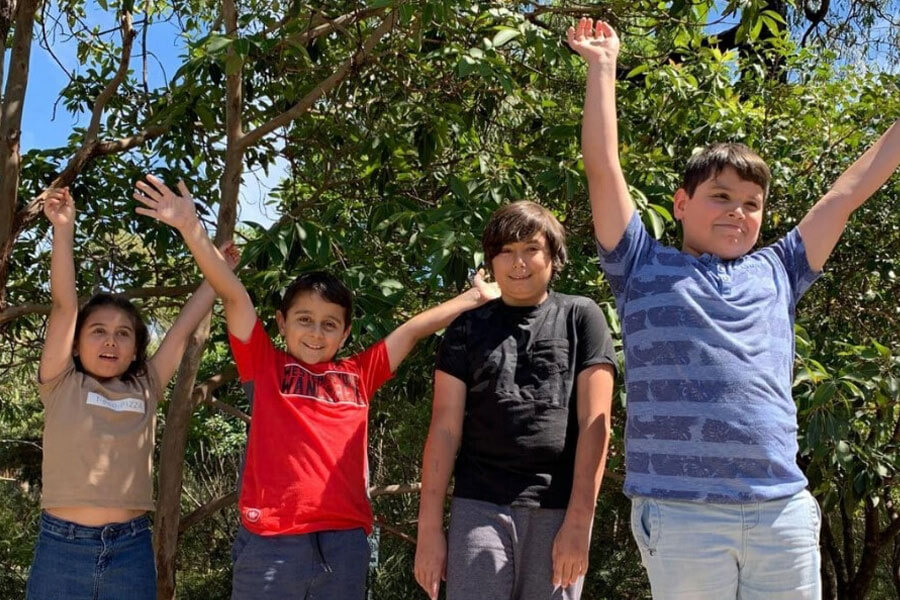 Four kids with arms in air laughing