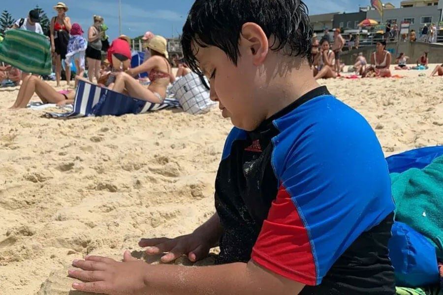 Young boy sitting on beach playing in sand