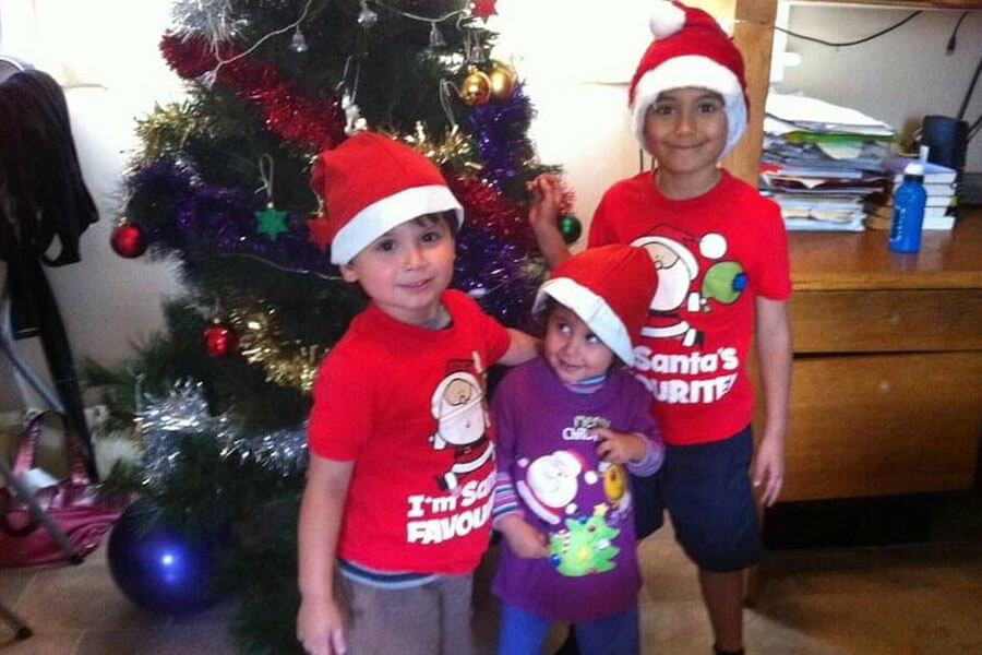 Three young kids wearing Santa hats standing in front of Christmas tree